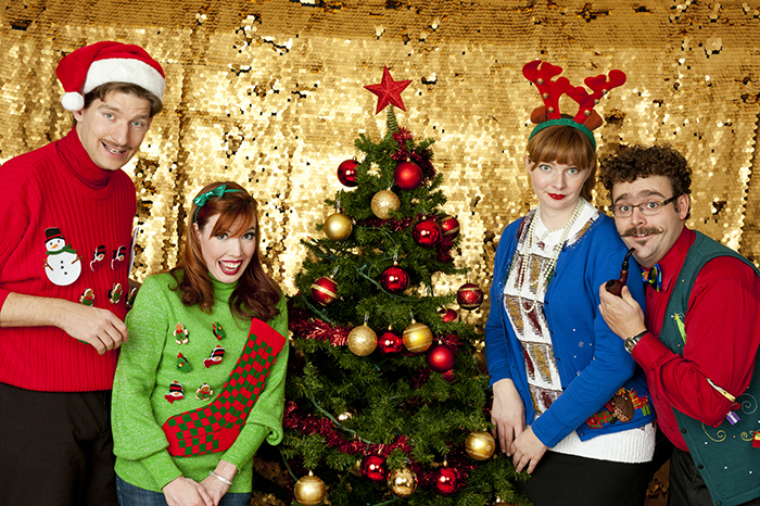 Ugly Christmas Sweater - A group of people fathered around a Christmas Tree wearing ugly Christmas Sweaters