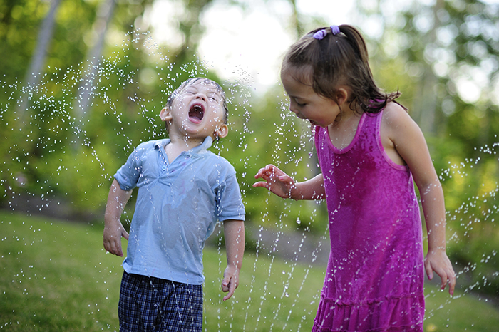 Summer Savings - A boy and girl playing in a sprinkler.