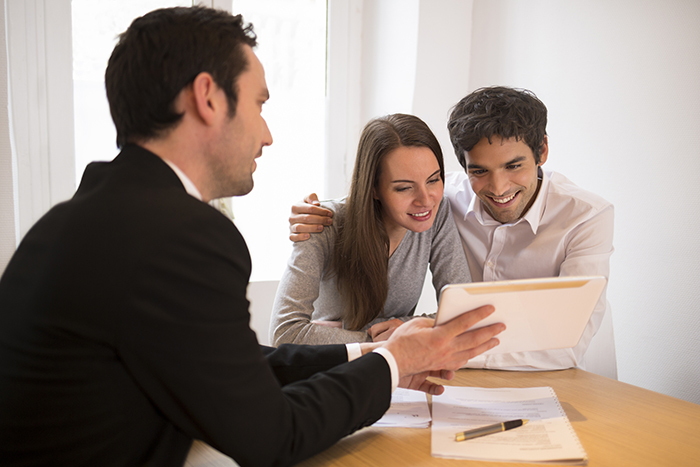 Credit Union Fees - Young couple looking over their mortgage pre-approval with a Credit Union home loan expert.