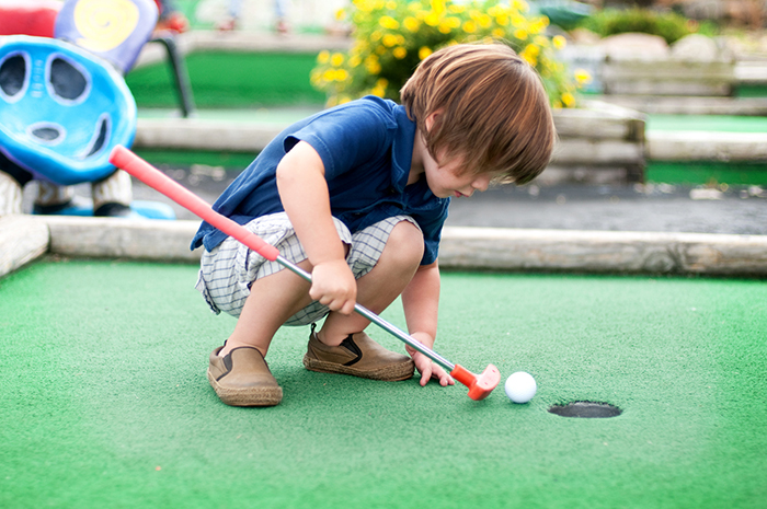 Summer Fun- Toddler trying to putt a golf ball into the hole at a miniature golf course.