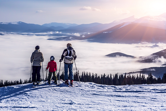 Holiday - Family of three people stays in front of scenic landscape. These are skiers, they dressed in winter sport jackets and have skies attached