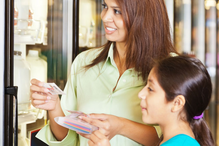 Ways to Save - Mom and daughter shopping with coupons at the grocery store.