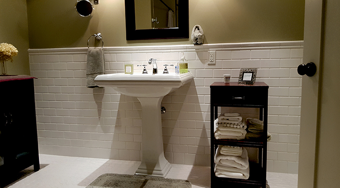 Home Repair - Updated bathroom with white subway tiles and white pedestal sink with cherry wood cabinets and mirror.