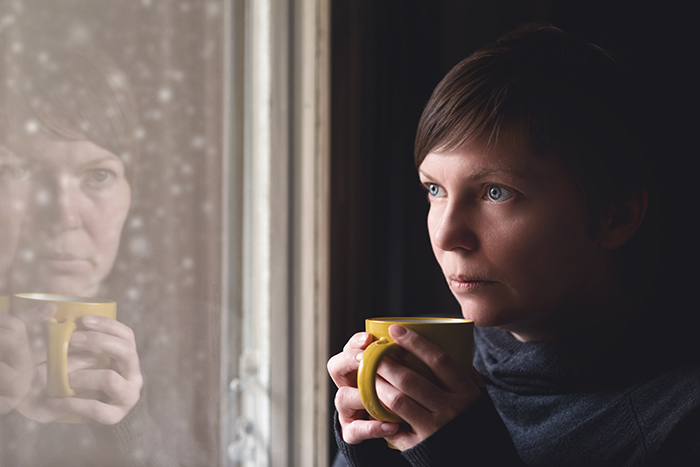Winter Blues - A woman looking forlornly out a window at the rain, snow and sleet. She is holding a yellow mug with tea.