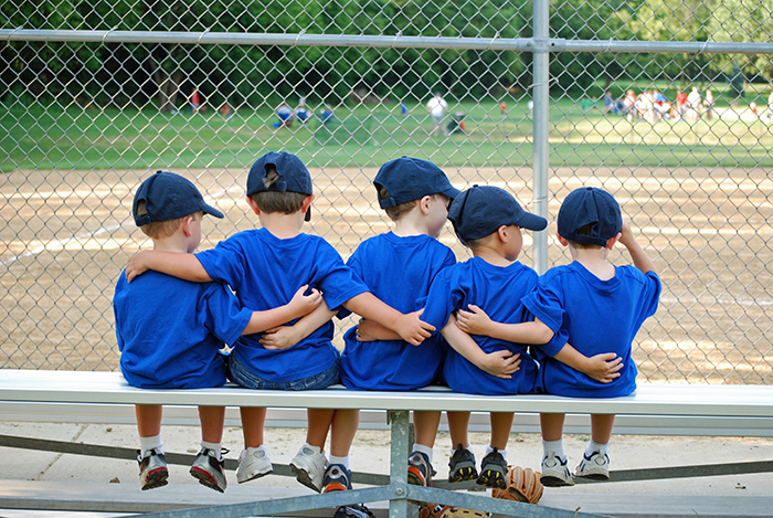 Youth Sports - Five little boys put their arms around each other before their baseball game.