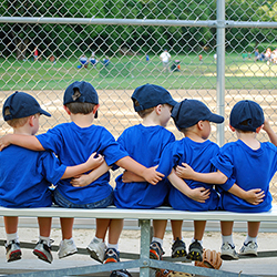 Youth Sports - Five little boys put their arms around each other befor their baseball game