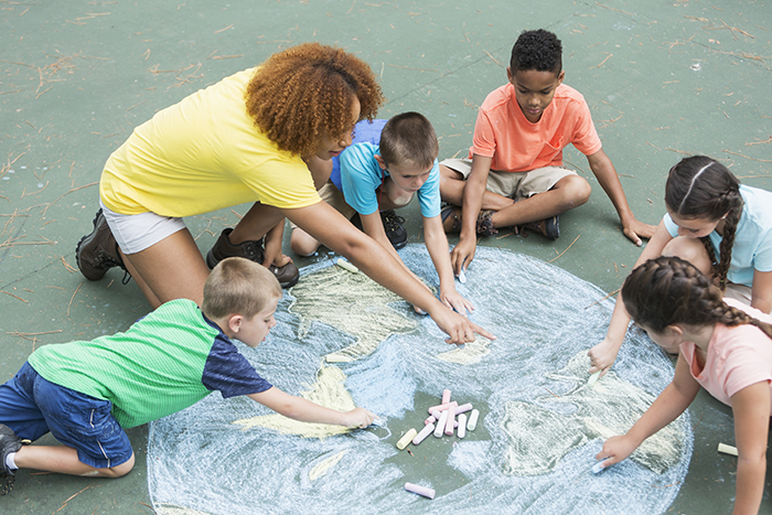 Go Green- A camp counselor with five multi-ethnic children at summer camp, sitting on a playground, working together to make a large chalk drawing of planet earth.