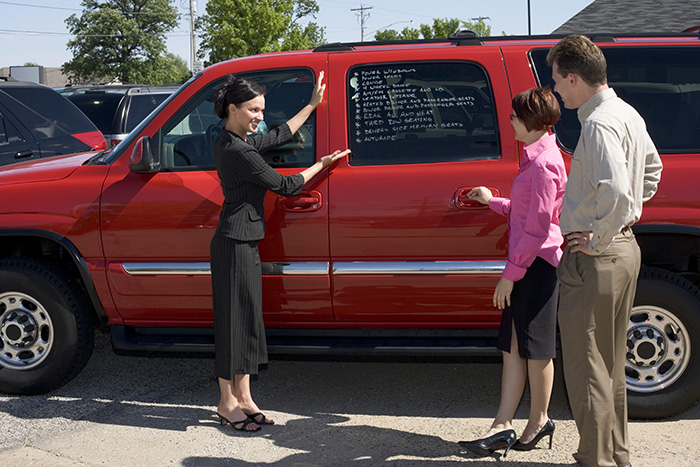 Buy a Used Car - Young couple looking at a red SUV at a car lot while the saleswoman talks about the features of the vehicle.