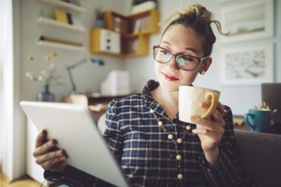 woman with glasses drinking coffee and looking at an iPad